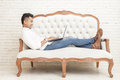 Asian young man sitting relax on sofa while working on laptop at full view photo home Royalty Free Stock Photos