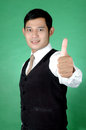Asian young man thumbs up against green background Royalty Free Stock Images