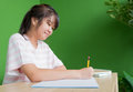 Asian young teenager girl writing homework at school library tab Royalty Free Stock Photo
