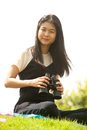 Asian young  woman sit on mound seeking binoculars . Royalty Free Stock Photo