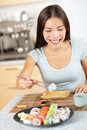 Asian young woman taking healthy lifestyle sushi pretty mixed race caucasian model from plate about to eat happily smiling looking Royalty Free Stock Photo