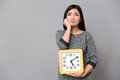 Asian young woman waiting and holding big clock Royalty Free Stock Photo