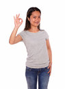 Asiatic smiling young woman showing you ok sign portrait of an on blue jeans and gray t shirt against white background Royalty Free Stock Image