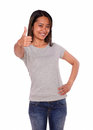 Asiatic young woman showing you ok sign portrait of an on blue jeans and gray t shirt against white background Royalty Free Stock Photo
