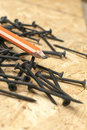Askew view of carpenters pencil and black nails