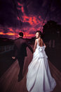 Askiz, Khakassia, Russia - August 17, 2013: Wedding, bride and groom go into bloody sunset. Royalty Free Stock Photo