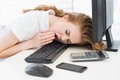 Asleep businesswoman yawning on keyboard at office young resting head while in the Royalty Free Stock Photography