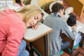 Asleep female with students sitting in lecture hall sleeping the college Stock Image
