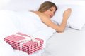 Asleep woman has surprise present waiting for her in bed beautiful young sleeping on with presents Royalty Free Stock Images