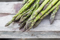 Asparagus with metallic lattice, wooden surface Royalty Free Stock Photo