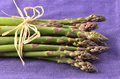 Asparagus on purple napkin fresh raw bunch in horizontal format Royalty Free Stock Image