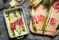 Asparagus rolled in ham and baked with cheese on old wooden cutting board Royalty Free Stock Photography