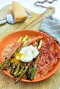 Asparagus wrapped in bacon slices with poched egg and parmesan Royalty Free Stock Photo