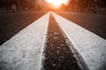 Asphalt city road with white lines ahead and the sunset Royalty Free Stock Photography