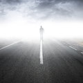 Asphalt highway perspective with walking man in the fog Royalty Free Stock Image