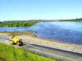 Asphalt paving machine on the river embankment new in a sunny day Stock Photo