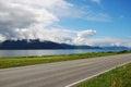Asphalt road along the blue fjord.