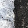 Asphalt road covered with white snow. Minimalistic natural background. Royalty Free Stock Photo