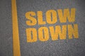 Asphalt road with text slow down near yellow line