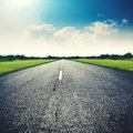 Asphalt road under wide blue skies Royalty Free Stock Photo