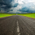 Asphault road in green field over blue sky old broken cloudy Stock Photos