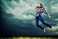 Aspiration beautiful young woman jumping in the field over stormy evening sky Royalty Free Stock Photo