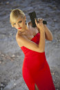Assassin in red with gun beautiful dress playing a spy Stock Photo