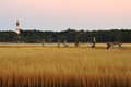 The assateague lighthouse and marsh at dusk old broken down old pier with grasses low tide late evening off coast of virginia Royalty Free Stock Image