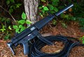 Assault rifle suppressed that is at a forest edge Stock Photos