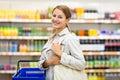 Assez jeune femme avec les épiceries de achat d un panier à provisions Images stock