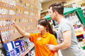 Assistant works with buyer at hardware shop young female seller helps purchaser choosing lamp in shopping mall supermarket Royalty Free Stock Photos