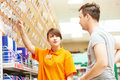 Assistant works with buyer at hardware shop young female seller helps purchaser choosing lamp in shopping mall supermarket Stock Images