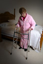 Assisted living nursing home elderly woman an old senior sits on her bed with a medical walker aid the female is alone and needs Royalty Free Stock Images