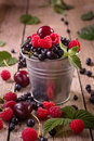 Assorted berries in pail small tin of Stock Images