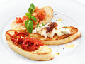 Assorted bruschetta with salmon air dry tomatoes or goat cheese served the basil leaf on a round white plate Stock Photography