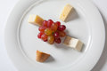 Assorted cheeses and grape on a white plate