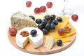 Assorted cheeses grapes and glass of wine on wooden board white Stock Photos