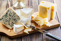 Assorted cheeses on wooden board Stock Photo