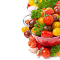 Assorted cherry tomatoes in a colander and fresh herbs isolated on white Royalty Free Stock Photography
