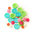 Assorted colorful craft buttons over white an assortment of shapes sizes and colors of round and flower shaped shot Stock Photo
