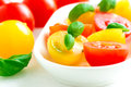 Assorted colorful red and yellow cherry tomatoes in plate on white tablecloth close up Royalty Free Stock Photos