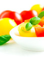 Assorted colorful red and yellow cherry tomatoes in plate on white tablecloth close up Stock Photography
