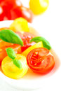 Assorted colorful red and yellow cherry tomatoes in plate on white tablecloth close up Royalty Free Stock Photography