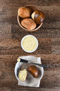 Assorted dinner rolls and butter crock bowl of with bread plate vertical format from a high angle Royalty Free Stock Image