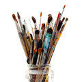 Assorted dirty painting brushes in glass flask Royalty Free Stock Photos