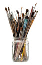 Assorted dirty painting brushes in glass flask Stock Image