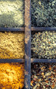 Assorted dried herbs and spices close up overhead view of in an old vintage wooden printers tray for use as seasoning Stock Image