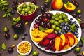 Assorted fresh berries of a cherry, gooseberry, blueberries, slices of ripe peach, plum and apricot, fragrant mint on a plate Royalty Free Stock Photo