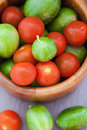 Assorted fresh colorful cucumbers and cherry tomatoes round in wooden bowl top view Royalty Free Stock Images