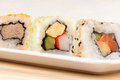Assorted maki sushi rolls japanese on a white plate over a wooden background selective focus Royalty Free Stock Photos